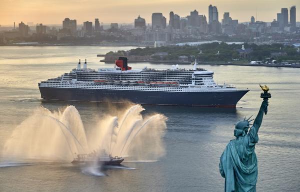 Le Queen Mary 2 devant la statue de la liberté, saluée par les pompiers de New York